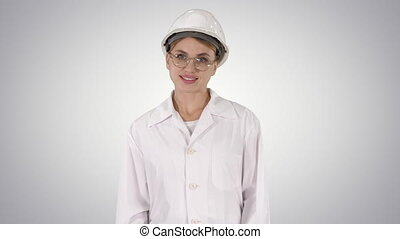 Professional woman in lab coat and gradient hardhat walking...