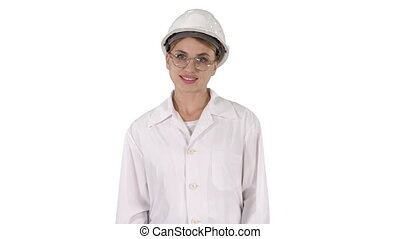 Professional woman in lab coat and white hardhat walking and...