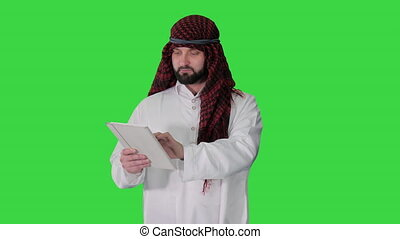 Sheikh presenting information or product using digital tablet on a Green Screen, Chroma Key.