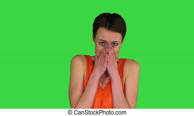 Medium shot. Shocked or surprised young woman in orange sundress on a Green Screen, Chroma Key. Professional shot in 4K resolution. 023. You can use it e.g. in your commercial video, business, presentation, broadcast