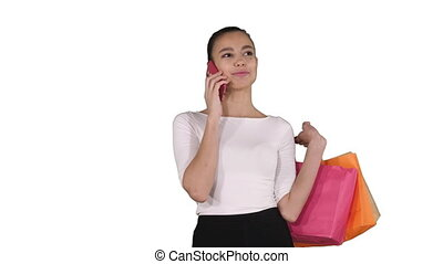 Shopping woman with bags talking on the phone on white background.