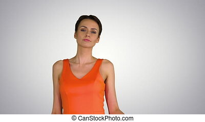 Medium shot. Short-haircutted pretty woman dancing in orange sundress on gradient background. Professional shot in 4K resolution. 023. You can use it e.g. in your commercial video, business, presentation, broadcast