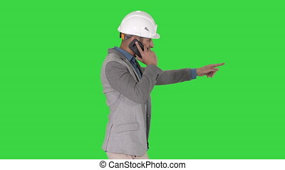 Architect engineer makes a phone call complaining about the results of work Pointing to the objects in front on a Green Screen, Chroma Key.