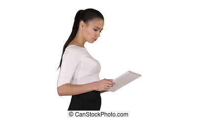 Attractive businesswoman using a digital tablet while walking on white background.