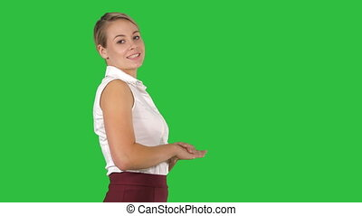 Attractive businesswoman walking and talking to the camera on a Green Screen, Chroma Key.