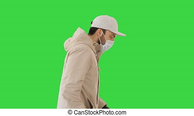 Ault man in jacket and in medical mask running on a Green Screen, Chroma Key.