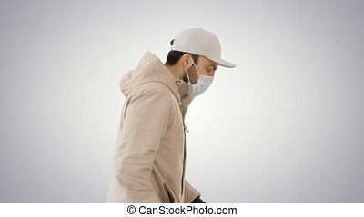 Ault man in jacket and in medical mask running on gradient background.