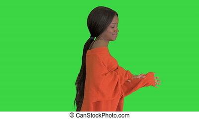 Beautiful black woman having fun smiling and dancing on a Green Screen, Chroma Key.