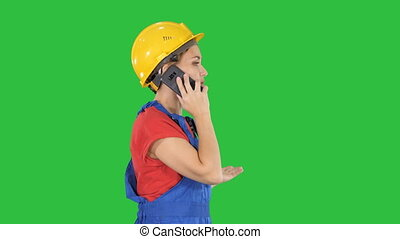 Beautiful young builder woman wear a yellow safety helmet making a call on a Green Screen, Chroma Key.