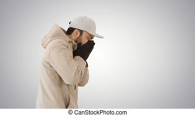 Caucasian man in a hat and coat coughing walking on gradient background.