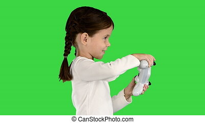 Medium shot. Side view. Close up. Excited little girl play videogame holding joystick in her hands on a Green Screen, Chroma Key. Professional shot in 4K resolution. 060. You can use it e.g. in your medical, commercial video, business, presentation, broadcast