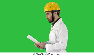 Contractor engineer walking with papers and checking arround on a Green Screen, Chroma Key.