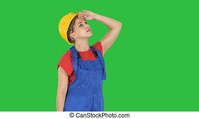 Engineer construction worker woman looking up amazed on a Green Screen, Chroma Key.