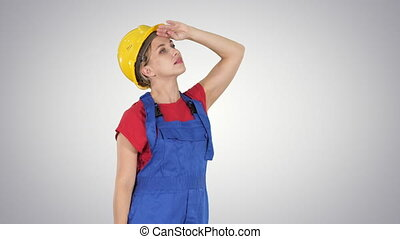 Engineer construction worker woman looking up amazed on gradient background.