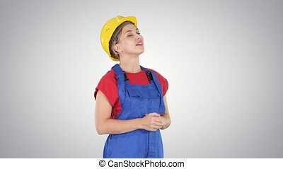 Engineer construction worker woman looking up at something amazing and laughing on gradient background.