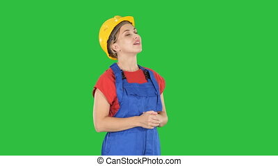 Engineer construction worker woman looking up at something amazing and laughing on a Green Screen, Chroma Key.