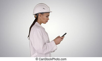Medium shot. Side view. Engineer using mobile phone texting while walking on gradient background. Professional shot in 4K resolution. 013. You can use it e.g. in your commercial video, business, presentation, broadcast