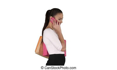 Excited woman talking on mobile phone with shopping bags on...