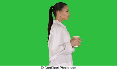 Female doctor drinking coffee and walking on a Green Screen, Chroma Key.