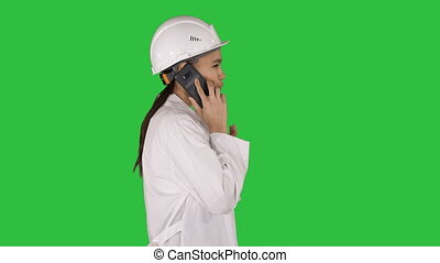 Female science engineer making a call while walking on a Green Screen, Chroma Key.