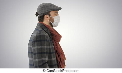 Gentleman wearing a protective face mask walking on gradient background.