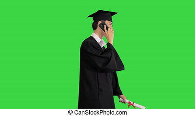 Medium shot. Side view. Graduating student starts walking and making a call on a Green Screen, Chroma Key. Professional shot in 4K resolution. 041. You can use it e.g. in your medical, commercial video, business, presentation, broadcast