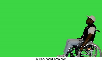 Medium shot. Side view. In and out of the frame. African American Person Driving by in a Wheelchair on a Green Screen, Chroma Key. Professional shot in 4K resolution. 065. You can use it e.g. in your medical, commercial video, business, presentation, broadcast