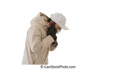 Man wears protective medical mask and talks on the phone walking on white background.
