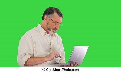 Medium shot. Side view. Mature man in glasses happy to finish the work on laptop on time on a Green Screen, Chroma Key. Professional shot in 4K resolution. 059. You can use it e.g. in your medical, commercial video, business, presentation, broadcast