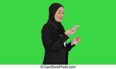 Medium shot. Side view. Muslim girl in hijab using smartphone to send voice messages on a Green Screen, Chroma Key. Professional shot in 4K resolution. 043. You can use it e.g. in your medical, commercial video, business, presentation, broadcast