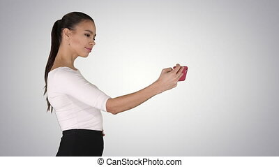 Pretty girl taking a selfie and walking on gradient background.