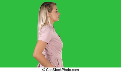 Pretty woman walks on a Green Screen, Chroma Key.