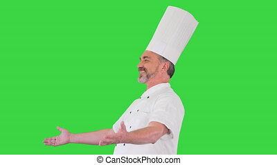 Medium shot. Side view. Senior chef welcoming guests of his restaurant on a Green Screen, Chroma Key. Professional shot in 4K resolution. 059. You can use it e.g. in your medical, commercial video, business, presentation, broadcast