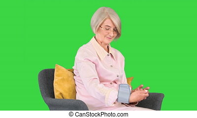 Medium shot. Side view. Senior woman looking at her blood pressure on the monitor Normal blood pressure on a Green Screen, Chroma Key. Professional shot in 4K resolution. 063. You can use it e.g. in your medical, commercial video, business, presentation, broadcast