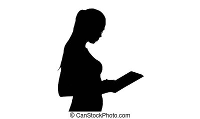 Silhouette Attractive businesswoman using a digital tablet while walking.