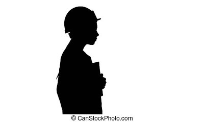 Silhouette Attractive Hispanic woman in white lab coat and white safety hard hat walking holding notebook or tablet.