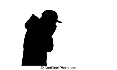 Medium shot. Side view. Silhouette Caucasian man in a hat and coat coughing walking. Professional shot in 4K resolution. 53. You can use it e.g. in your medical, commercial video, business, presentation, broadcast