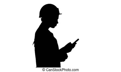 Medium shot. Side view. Silhouette Engineer using mobile phone texting while walking. Professional shot in 4K resolution. 013. You can use it e.g. in your commercial video, business, presentation, broadcast