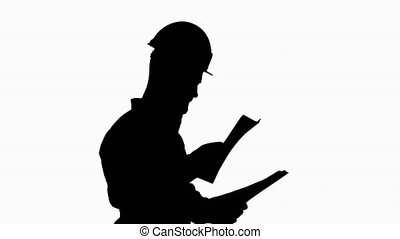 Silhouette Male engineer walking in a hard hat looking at ...