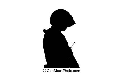 Medium shot. Side view. Silhouette Swat operator with assault rifle walking. Professional shot in 4K resolution. 067. You can use it e.g. in your medical, commercial video, business, presentation, broadcast