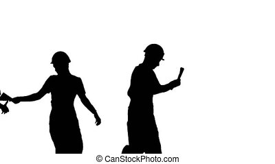 Medium shot. Side view. Silhouette Three young construction workers in hardhats passing on documents while doing a silly walk in a row. Professional shot in 4K resolution. 045. You can use it e.g. in your medical, commercial video, business, presentation, broadcast