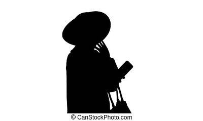 Medium shot. Side view. Smiling african american woman wearing fashion coat and a black hat taking selfie while walking, Alpha Channel Professional shot in 4K resolution. 046. You can use it e.g. in your medical, commercial video, business, presentation, broadcast