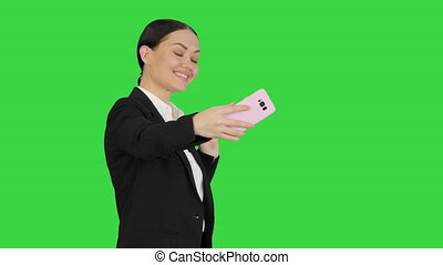 Medium shot. Side view. Smiling Businesswoman taking selfie on her phone while walking on a Green Screen, Chroma Key. Professional shot in 4K resolution. 043. You can use it e.g. in your medical, commercial video, business, presentation, broadcast