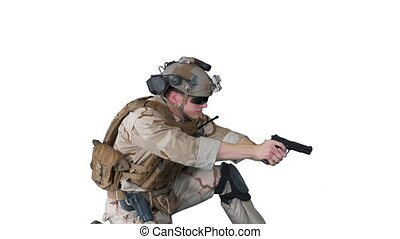 Medium shot. Side view. Soldier is shooting from pistol sitting on his knee on white background. Professional shot in 4K resolution. 048. You can use it e.g. in your medical, commercial video, business, presentation, broadcast