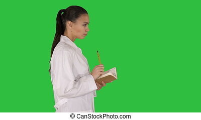 Successful medical doctors making notes while walking on a Green Screen, Chroma Key.