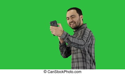 Teenage boy making a selfie when walking on a Green Screen, Chroma Key.