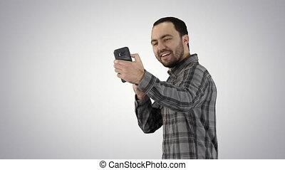 Teenage boy making a selfie when walking on gradient background.