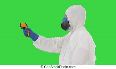 Temperature check on a corona virus Doctor in protective suit with pyrometer on a Green Screen, Chroma Key.