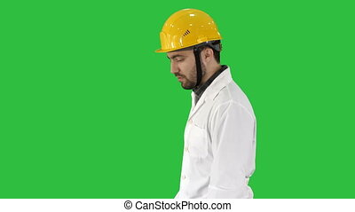 Unhappy construction site engineer talking and walking on a Green Screen, Chroma Key.