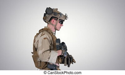 Medium shot. Side view. US Army ranger in uniform and weapon walking on gradient background. Professional shot in 4K resolution. 4151. You can use it e.g. in your commercial video, business, presentation, broadcast